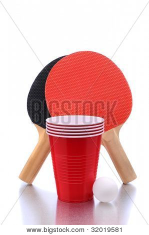 Ping Pong paddles and ball with cups for playing Beer Pong on a white background with reflection.