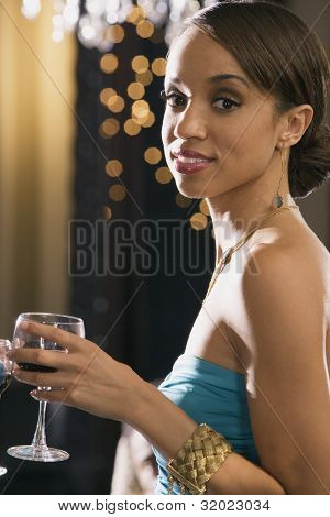 Portrait of African woman holding wine glass
