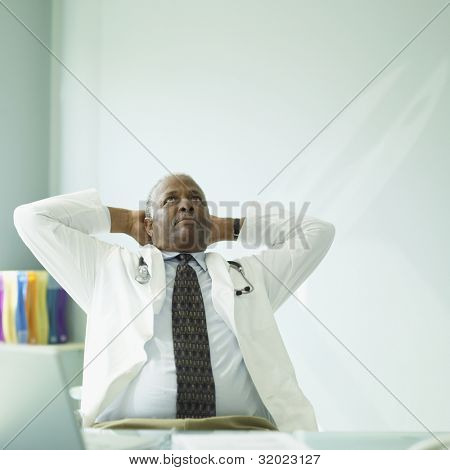 Senior African male doctor with arms behind head