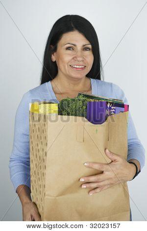 Hispanic woman carrying grocery bag