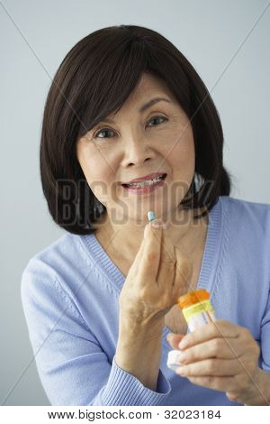 Senior Asian woman taking medication
