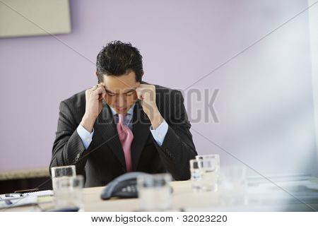 Asian businessman with head in hands