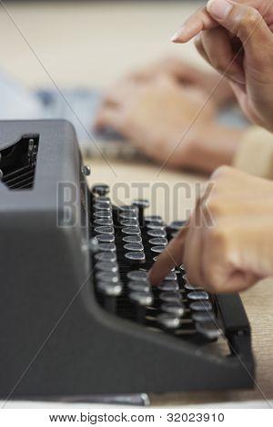 Businesswoman typing on typewriter