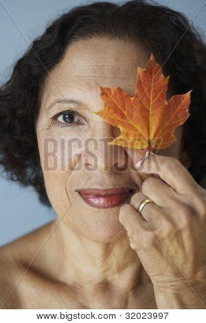 Senior African woman holding autumn leaf over eye