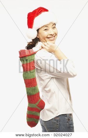 Portrait of Asian woman holding Christmas stocking