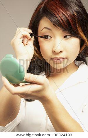 Asian woman applying mascara