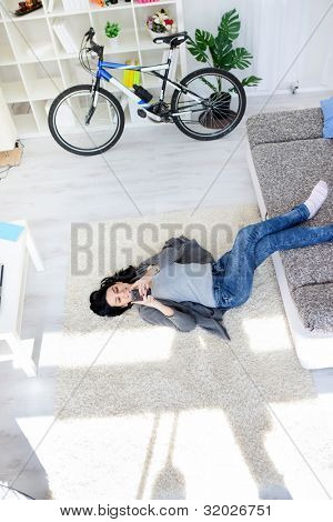 Young girl lying on floor in living room and listening music through smart phone