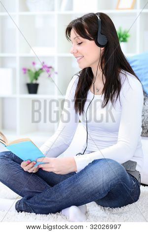 Young girl reading book and listening music, enjoying time