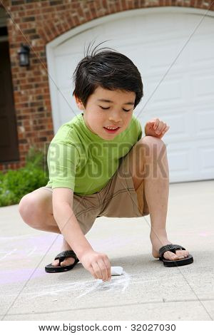 Child playing with chalk in the driveway