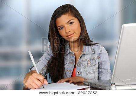 Chica escribiendo en su escritorio en la escuela
