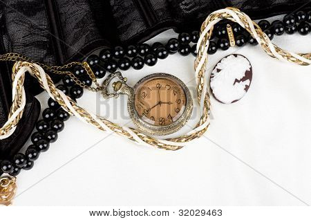 Black lace with form flower, clock and antique cameo on white background
