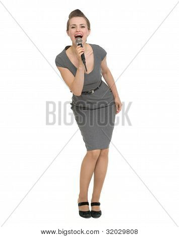 Full Length Portrait Of Happy Woman Singing In Microphone Isolated