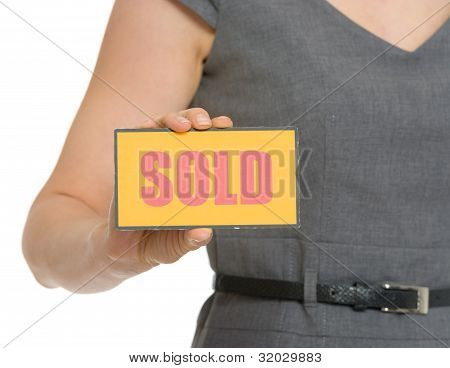 Closeup On Sold Sign In Female Hand Isolated