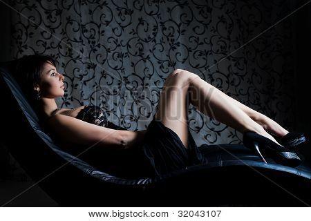 garota sexy em vestido de noite, deitado no sofá