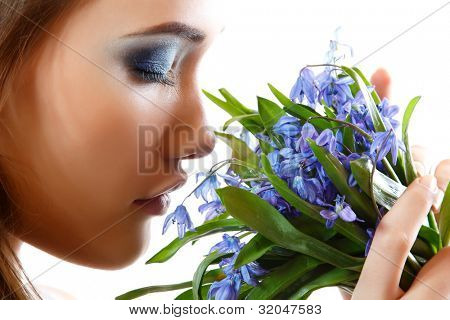 Beautiful teen girl smell and enjoy fragrance of snowdrop flowers. isolated on white background