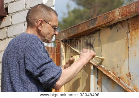 Man painting old rusted gate.  Ukraine