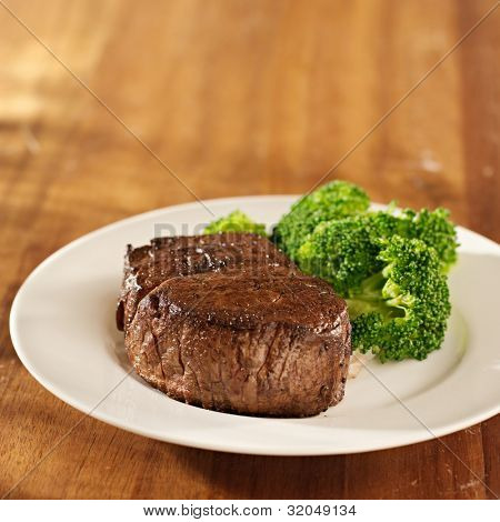 beef steak fillet with broccoli and copy space composition on wood surface