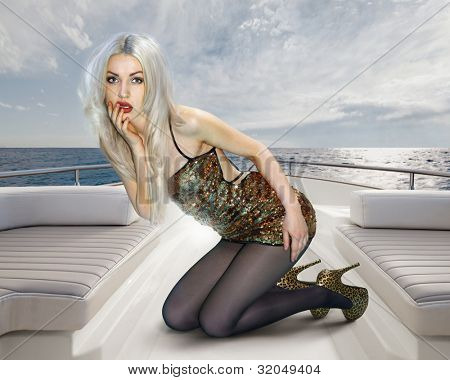 Young attractive blonde woman in shining dress on deck of yacht
