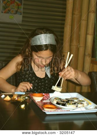 Young Girl Eating Sushi With Chopsticks