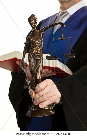 a judge with a law book in court. with justice figure in the hand.