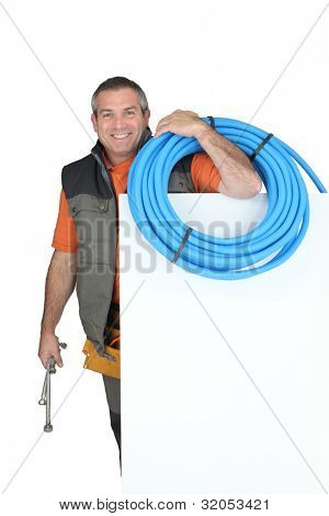 Smiling man with blank board and blue tube