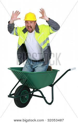Laborer sitting in a wheelbarrow screaming