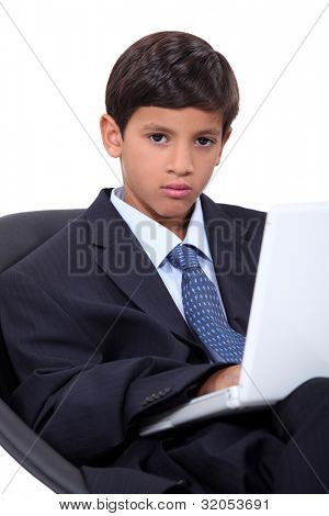 Serious young boy in an adult business suit with a laptop computer
