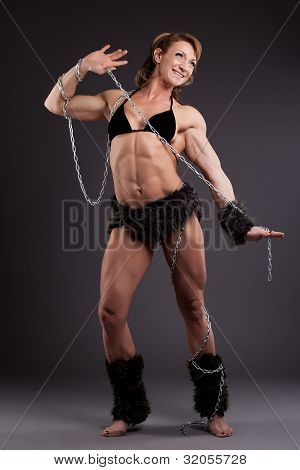 Strong woman body builder posing with chain