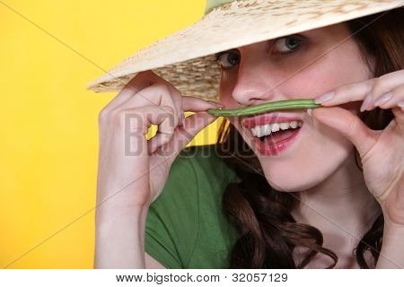Playful woman holding a green bean above her upper lip