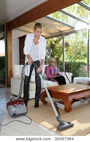 Woman vacuuming in senior woman's house
