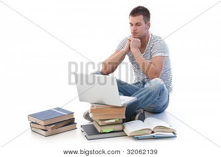 Young college student using laptop, sitting among books, using headset.