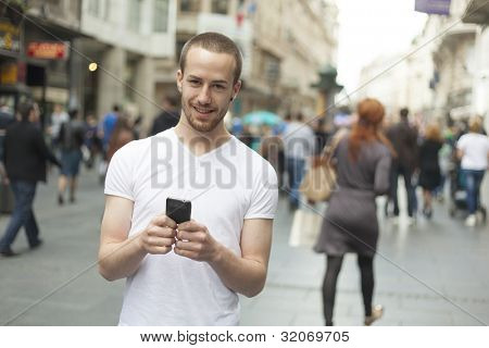 Smiling Man with mobile phone walking, background is blured city