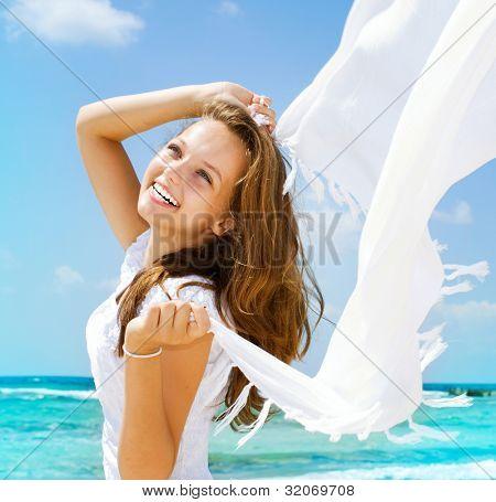 Hermosa chica con pañuelo blanco en la playa. Viajes y vacaciones. Concepto de libertad