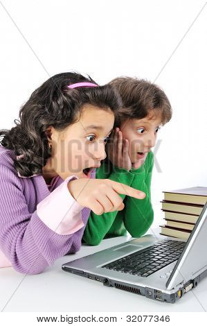 Two surprised girlfriends in front of laptop and stack of books