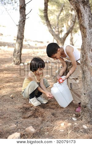 Helping in washing hands with water in nature, children summer camp