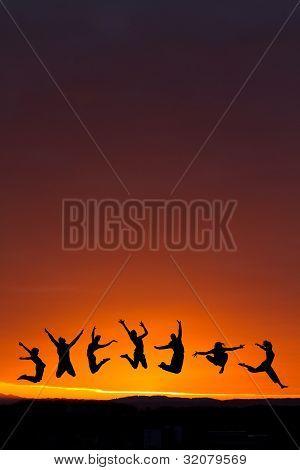 silueta de amigos saltando en la puesta del sol