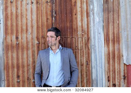 Businessman standing in front of sheet metal wall