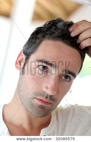 Man in front of mirrror looking at his hair