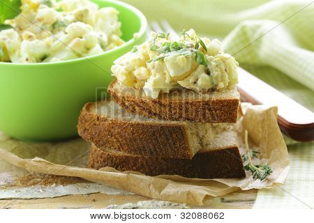 Egg salad in a green cup with black bread