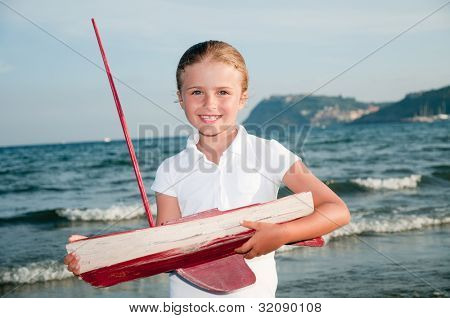 Summer vacation - portrait of lovely girl with yacht model at the beach