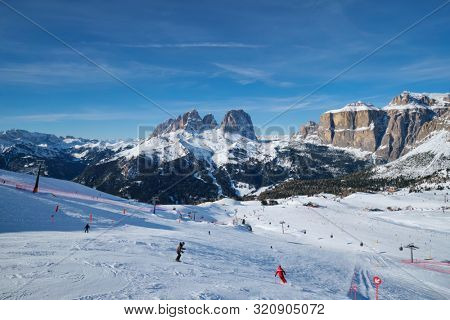 poster of View of a ski resort piste with people skiing in Dolomites in Italy. Ski area Belvedere. Canazei, It