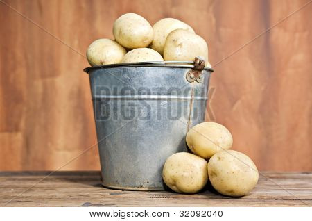 Old bucket filled with potatoes against a rustic background