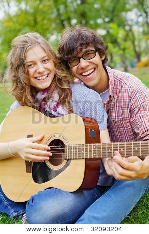 Joyful guy teaching beautiful teenage girl play guitar in summer park