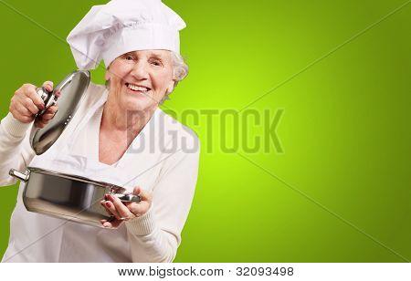 Retrato de mujer senior cocinar abrir una cacerola sobre un fondo verde