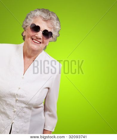 portrait of a happy senior woman wearing heart glasses over a green background