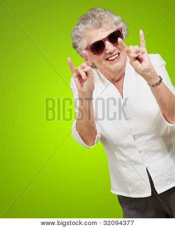 portrait of a happy senior woman doing a rock symbol over a green background