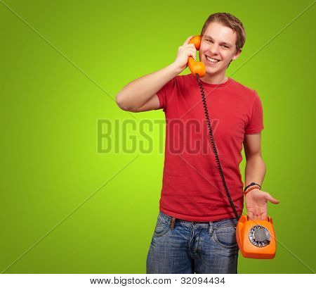 portrait of a young man talking with a vintage telephone over a green background