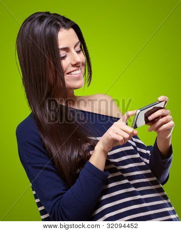 portrait of a young woman touching a modern mobile over a green background