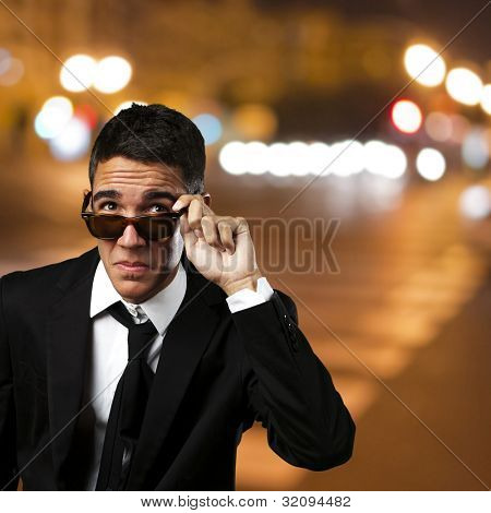 portrait of a business man taking off his sunglasses at city by night