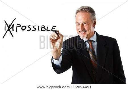 Motivation concept. Businessman changing the word impossible into possible